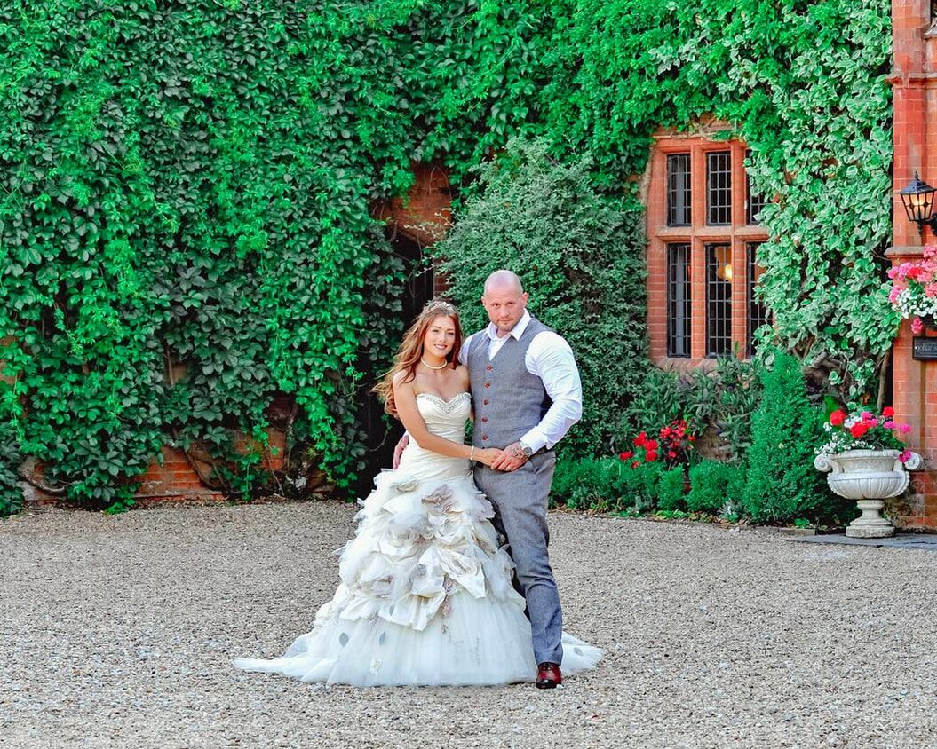 Picture Image of a bride and groom standing together in the front of their country house wedding venue