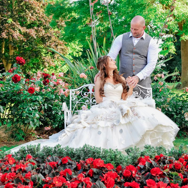 Picture Image of a bride and groom in a beautiful rose garden sat on a garden seat