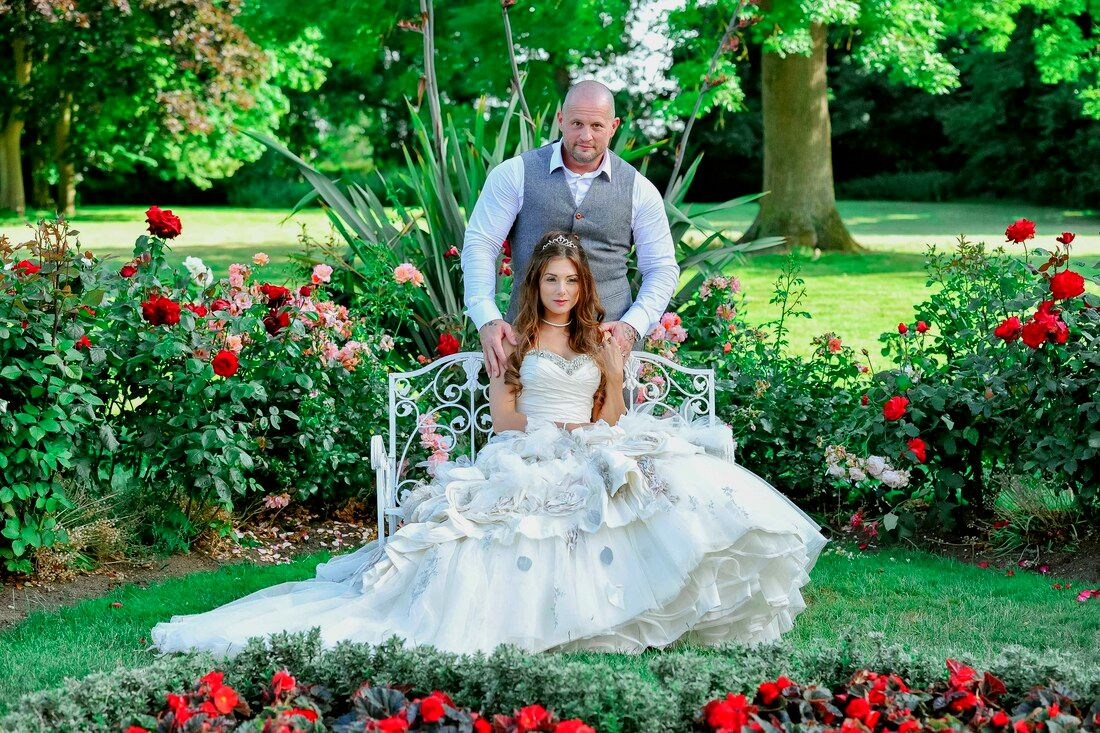 Picture Bride and groom sitting on a bench in the rose garden of a manor house rose garden