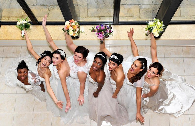 Picture image of nine brides in a line smiling on a special day