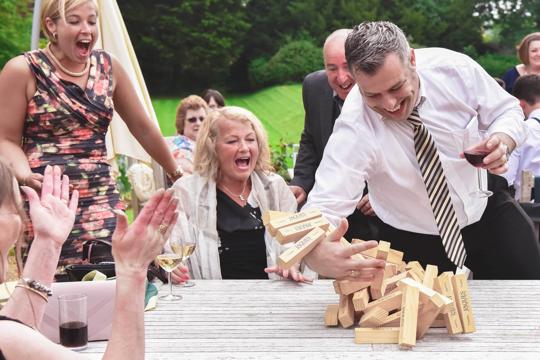 Wedding guests playing Jenga in the summer garden